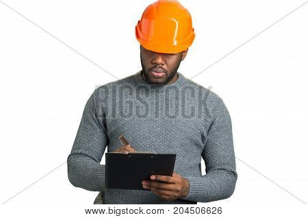 Serious engineer writing on clipboard. Building inspector writing on black clipboard isolated on white background.
