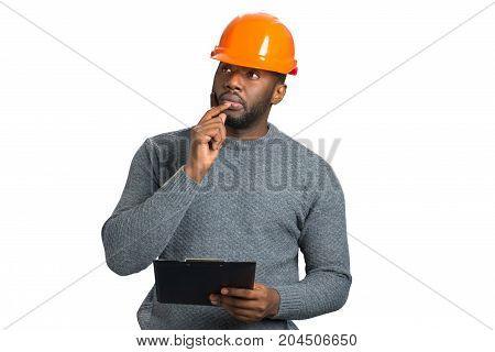 Thoughtful male architect with pen. Handsome architect in protective helmet thinking about day schedule. Pensive engineer with clipboard.