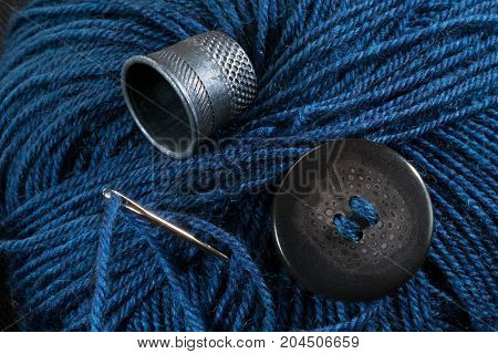 skein of yarn needle thimble and button