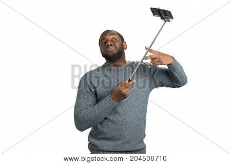 Beautiful man taking selfie with monopod. Afro american man posing with selfie stick in studio taking a photo of himself seriously.