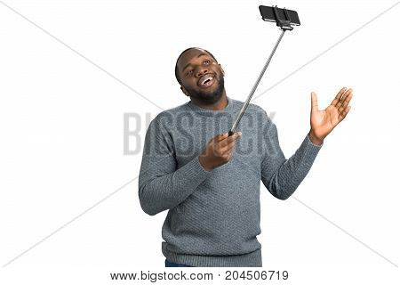 Smiling man taking video on monopod. Studio shot of happy young handsome man smiling and gesticulating while taking selfie picture with mobile phone on.