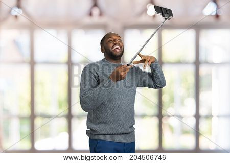 Laughing man, monopod, blurred background. Afro american man posing with selfie stick in studio taking a photo of himself smiling. Cheerful man in casual style gesticulating on selfie stick.