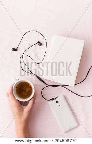 A Cup Of Herbal Tea In Hand On Bed With A Book And Music