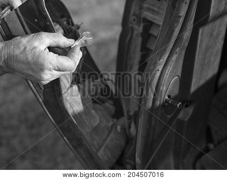 Mechanic replacing a blown brake bulb black and white photo