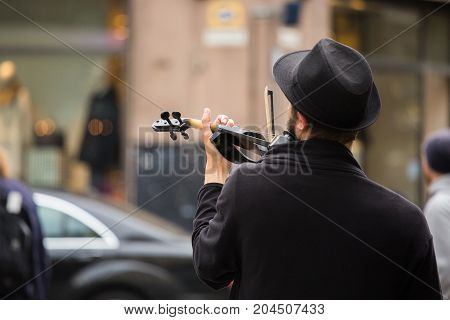 A street musician playing the violin in Europe