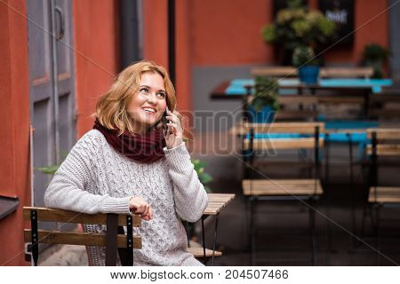 Woman is sitting in an outdoor cafe and talking on phone