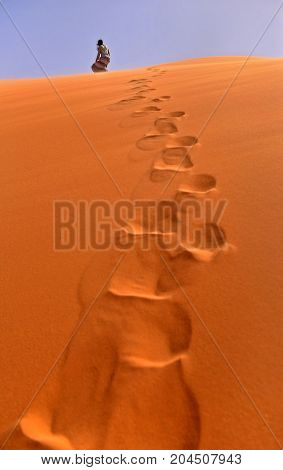 traces of the person on orange sand in the desert the person in the fluttering clothes at goes to a dune