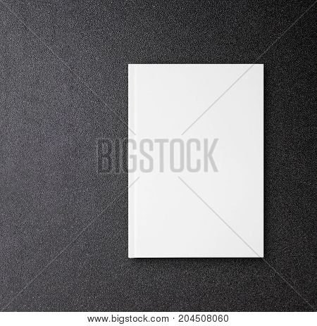 Blank white hardcover canvas book mockup for design book cover on black table.