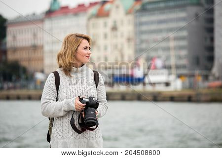 Woman with a camera on the seaside in Europe