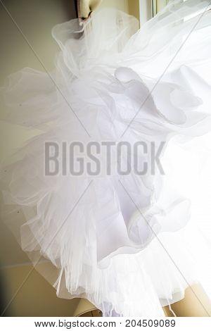 Beautiful white wedding gown hanging on window