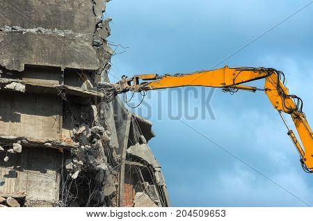 Remove dangerous building in an urban area with an excavator