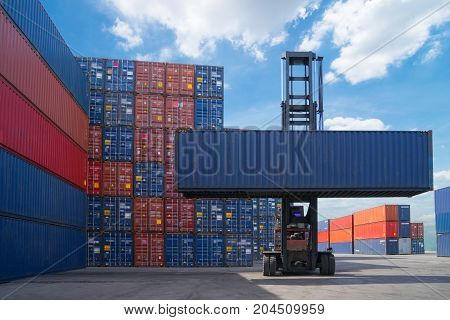 Forklift truck lifting cargo container in shipping yard or dock yard against sunrise sky with cargo container stack in background for transportation import, Export and logistic industrial concept