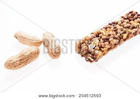 Two healthy granola bar (muesli or cereal bar) and peanuts isolated on white background