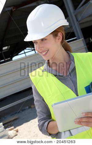 Woman engineer checking building plan on touch pad