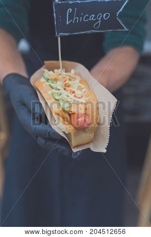 Street fast food festival, hot dog with grilled sausage. Cookout american bbq food, closeup in chef's hand in craft paper with text labels