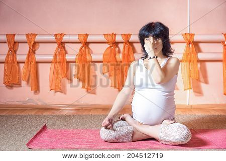 Healthy maternity lifestyle concept. 40 week pregnant middle aged caucasian woman in yoga classes sits in a lotus position and breathes through one nostril covering her nose with her hand.