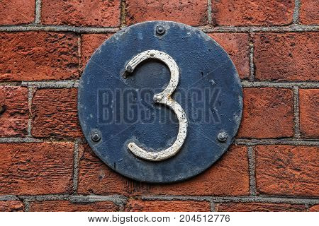 3 Digit On Dark Metal Background On Red Brick Wall.
