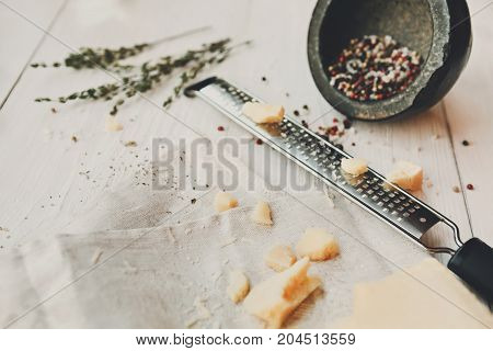 Parmesan pieces, grate, species and herbs on wooden table. Classic italian cuisine cooking ingredient, grated hard cheese. Shallow depth of field, selective focus