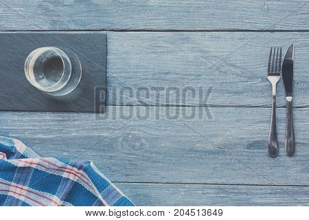 Blue rustic wood background. Served table, glass of water and cutlery, top view