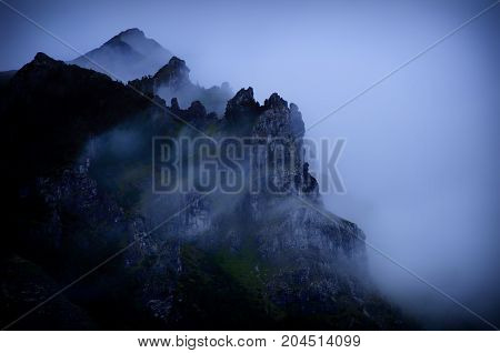 Spooky foggy mountains and woods in the evening (in dark blue tones)