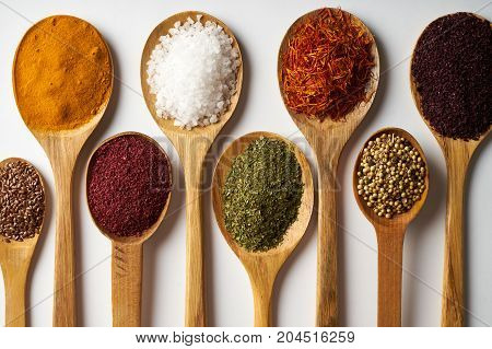 Spices In Wooden Spoons Isolated On White Background