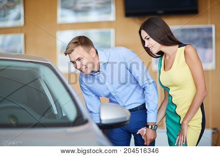 Buying a dream car. Portrait of a beautiful young couple buying a new car at the dealership handsome man laughing and hugging his wife while woman is showing thumbs up