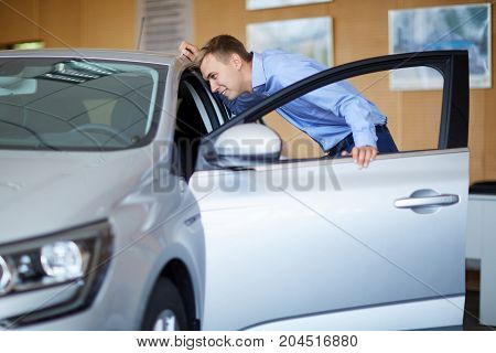 Beautiful young male is talking to handsome car dealership worker while choosing a car in dealership