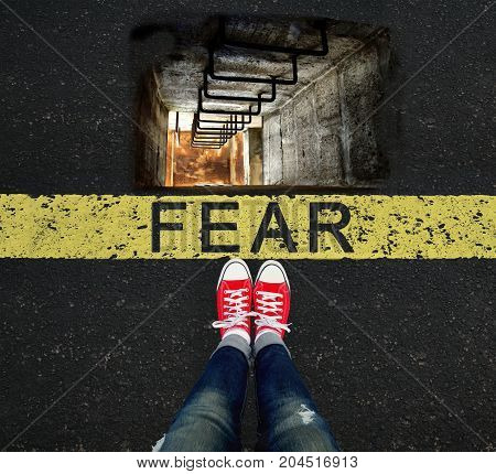 Girl standing in front of the FEAR sign and a well that scares