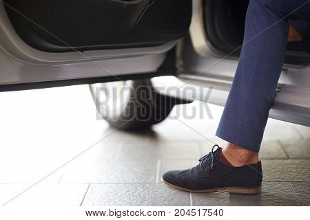 Image of body parts of man, who choos a new car in showroom.