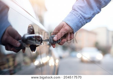 Hand holding a car key and opening the car door lock