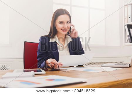 Business consulting. Young smiling businesswoman talking by phone at modern office workplace with coffee