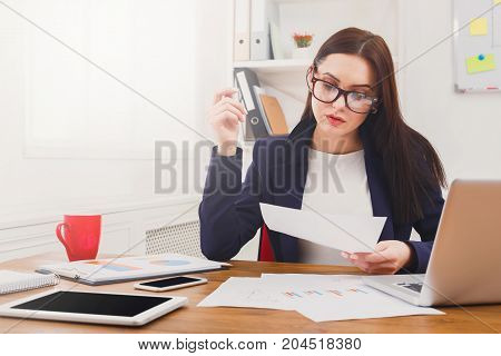 Paperwork. Serious business woman in formal wear sitting at wooden desk in modern office and reading report document, copy space