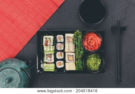 Colorful sushi and rolls platter in japanese restaurant, with teapot and chopsticks top view, copy space on mat