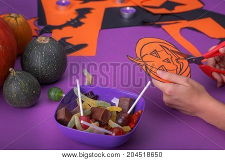 Cloud frame with ghost, candy, pumpkins, spiders and bats cut out of paper. Purple background.