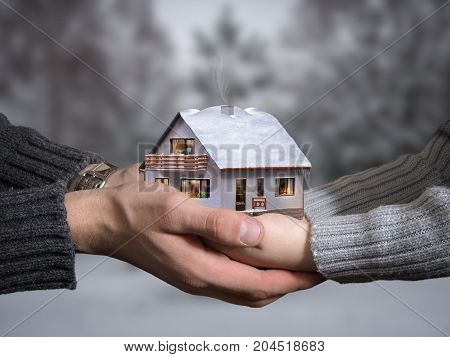 The hands of an adult and child hold a beautiful house. The concept of private housing buy a country house
