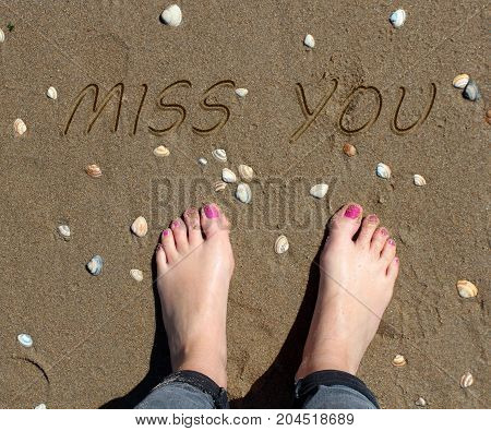 Miss you written on the sand at the foot of a girl