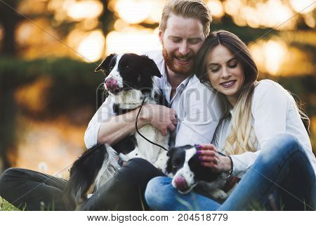 Beautiful couple walking dogs together and bonding in nature