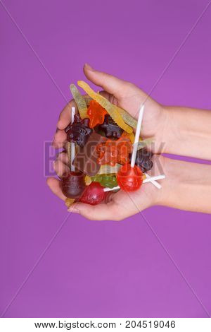 A lot of candies for babies holiday. Isolated on purple background.