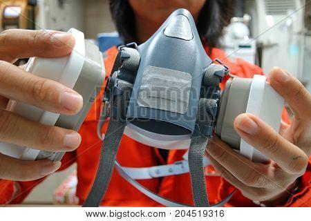 Multi-purpose respirator half mask for toxic gas protection.The man prepare to wear Multi-purpose respirator half mask.