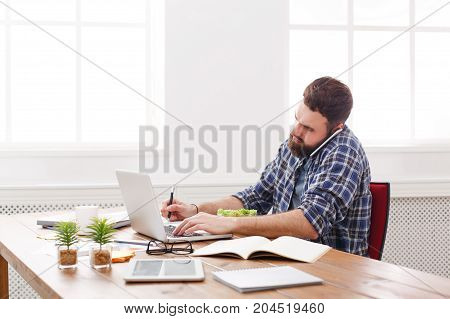 Busy man has business lunch in office, talking on mobile and makes note. Overworking concept.