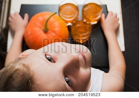 A little boy carrying a tray with pumpkin and drinks , a Halloween party,
