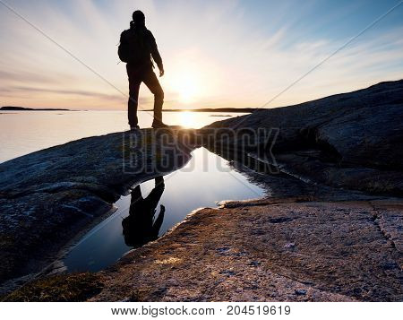Hiker In Dark Sportswear With Poles And Sporty Backpack. Coastline Trail On Rocky Shore. Alone Touri