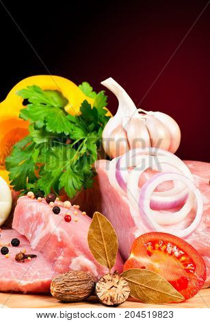 Raw pork with spices and vegetables on a cutting board over dark background