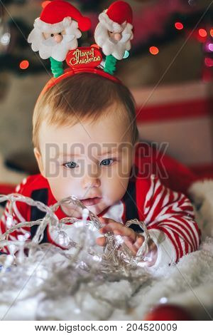 Funny baby boy wearing santa claus hat and suit playing with Christmas ball over Christmas tree in room. Holiday season.