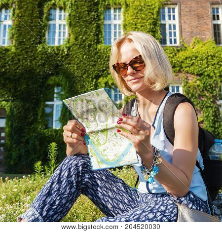 Female traveler sitting and studying the city map on the background of Sandomierz Watchtower in Wawel Royal Castle and former barracks. Krakow, Poland
