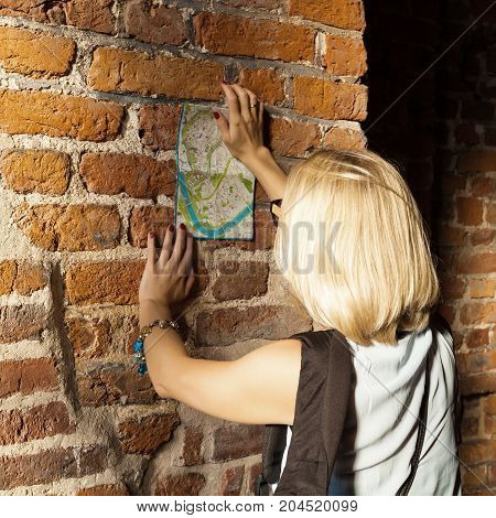 Female traveler stands and studying the city map on the background of old age brick wall within Sandomierz Watchtower in Wawel Royal Castle. Krakow, Poland