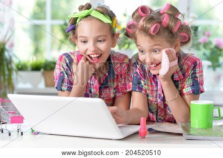 Two cute little girls sitting at table with laptop and beautifying themselves