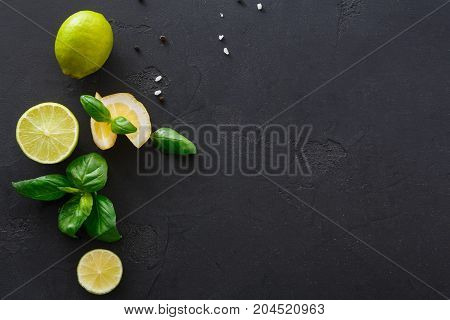 Lime and lemon with mint on black background, copy space. Ingredients for mojito preparing, top view