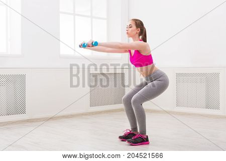 Young beautiful woman in sportswear doing squat exercises with dumbbells at gym on white background