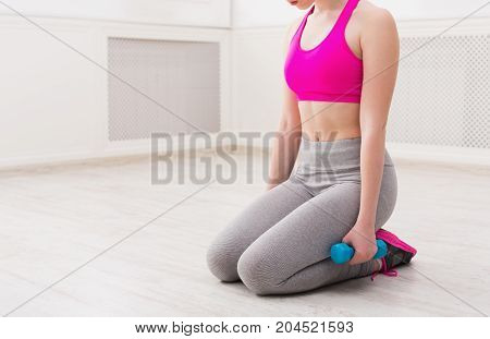 Young woman in sportswear sitting and holding dumbbells at gym on white background